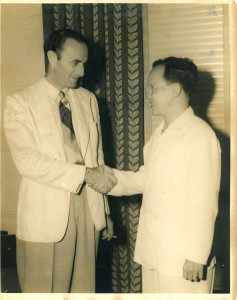 Accepting a congratulatory handshake from Dr. Herbert Zipper, conductor of the Manila Symphony; chairman of Republic March Contest Committee.
